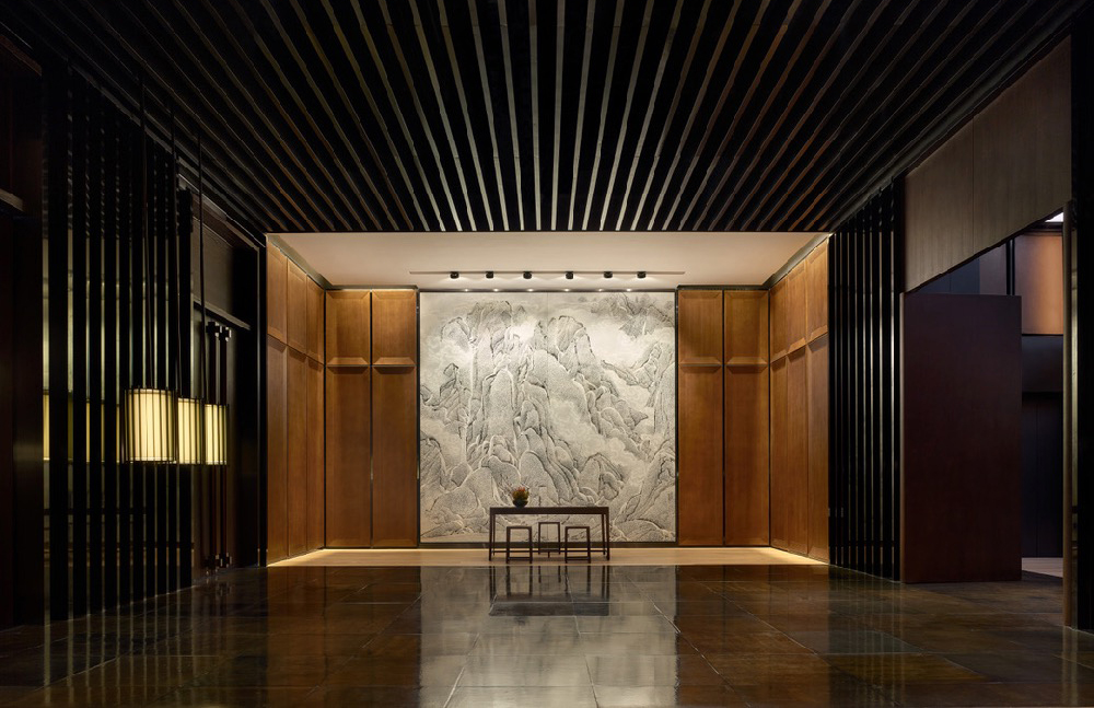 The sculptural lobby of the PuXuan Hotel and Spa which features dark and light woods, rubbed ceilings and polished stone floors