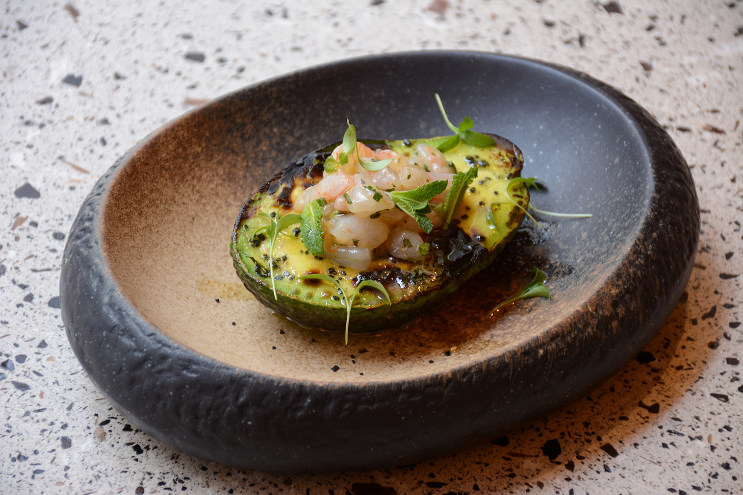 Grilled avocado topped by shrimp