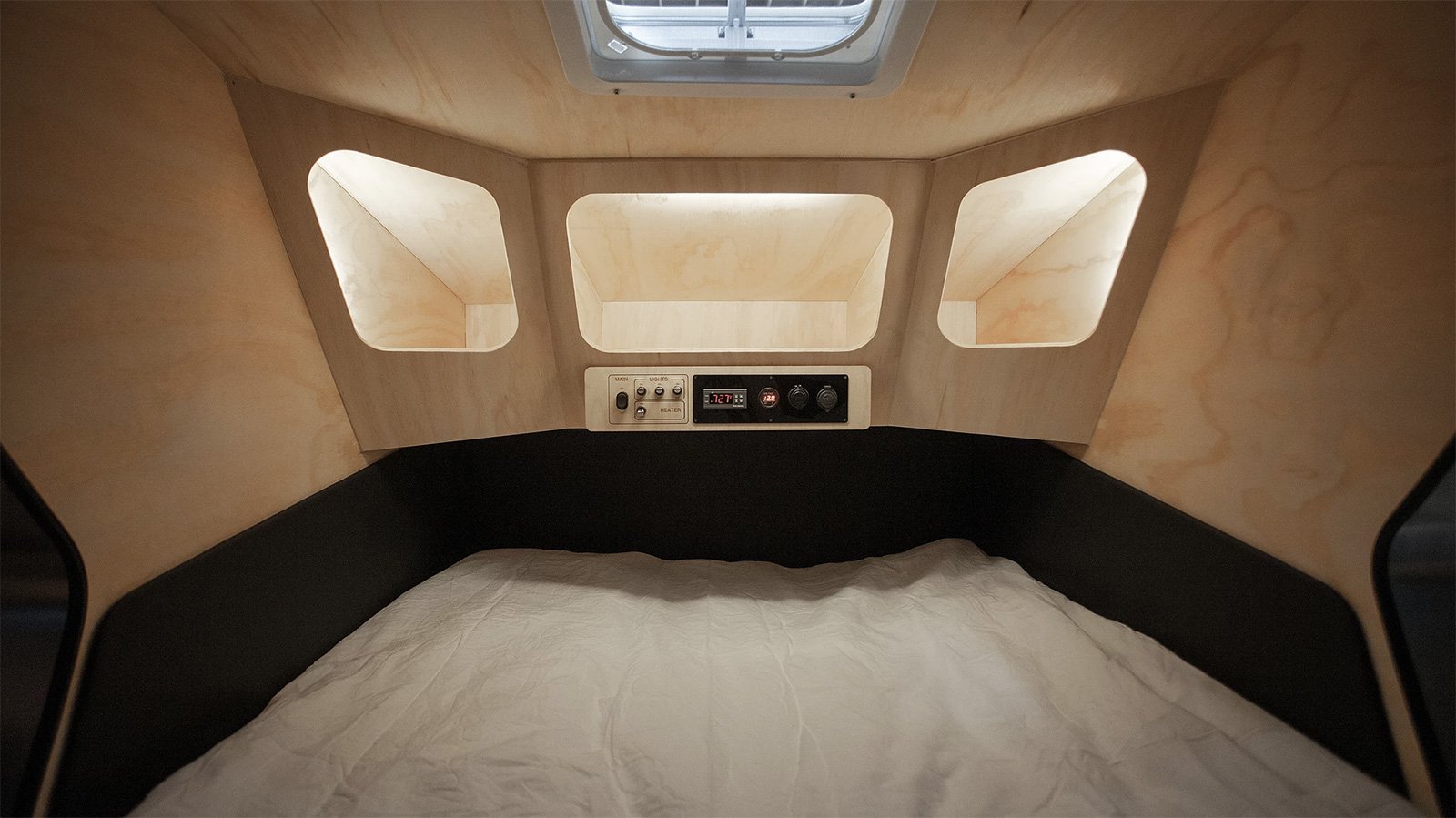 The Polydrop camper has pared back interiors with built-in cubby holes for storage and a panel for controlling LED lighting