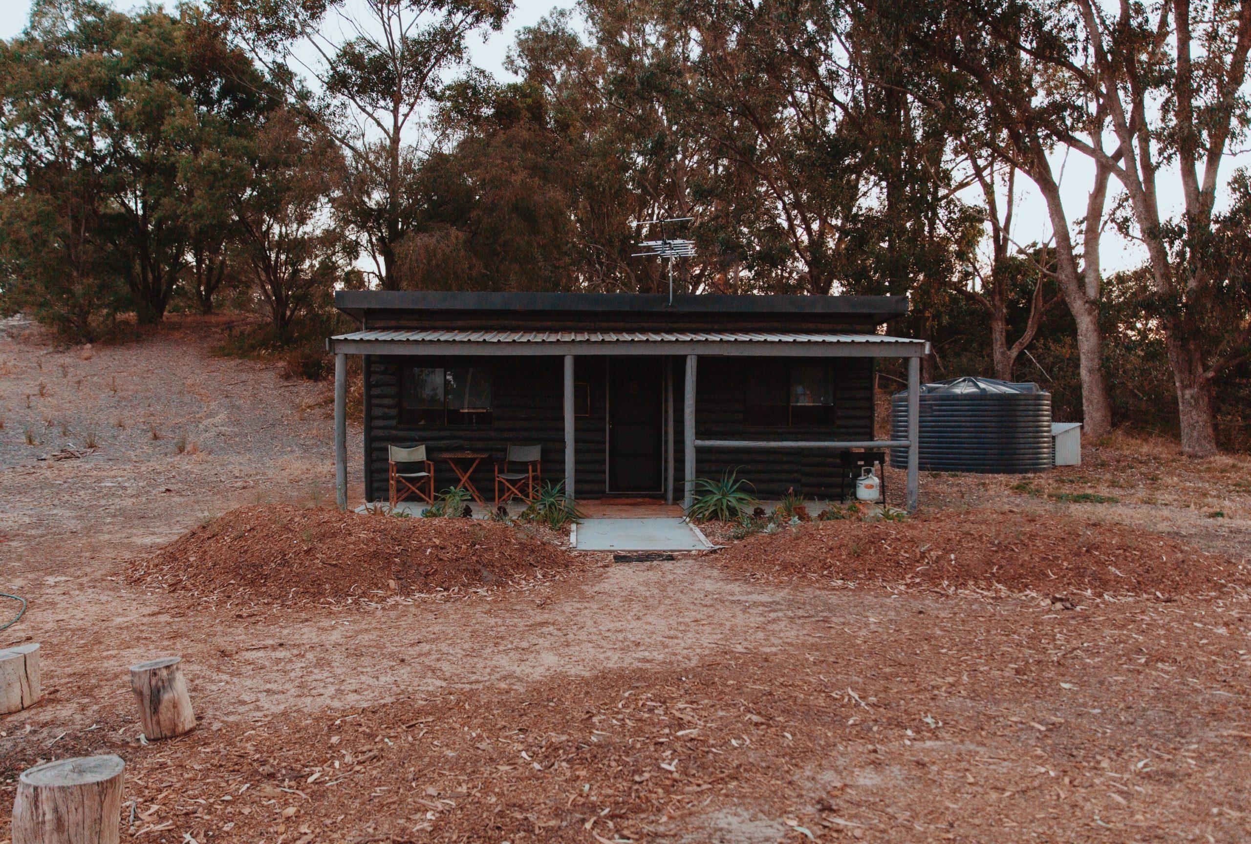 Log cabins nestle behind the sand dunes in Western Australia