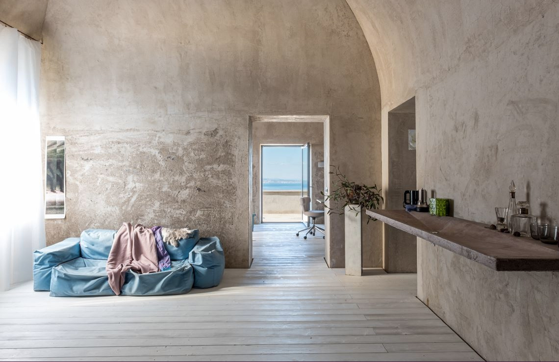 Raw plaster and tactile surfaces run across this converted olive oil mill in the foothills of Sorrento, Italy