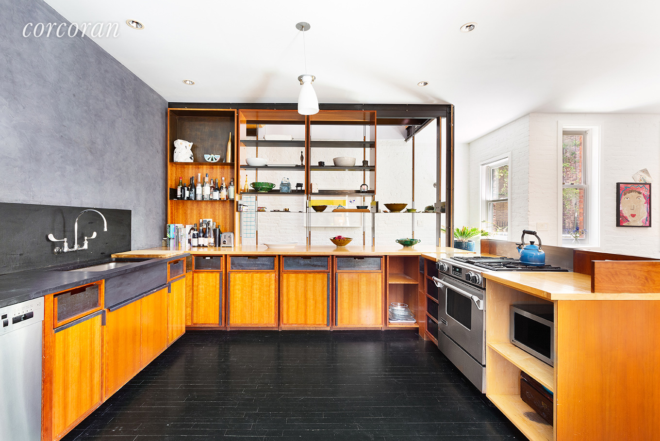 The Brooklyn carriage house has midcentury style teak cabinetry in the kitchen with modern stainless steel appliances.