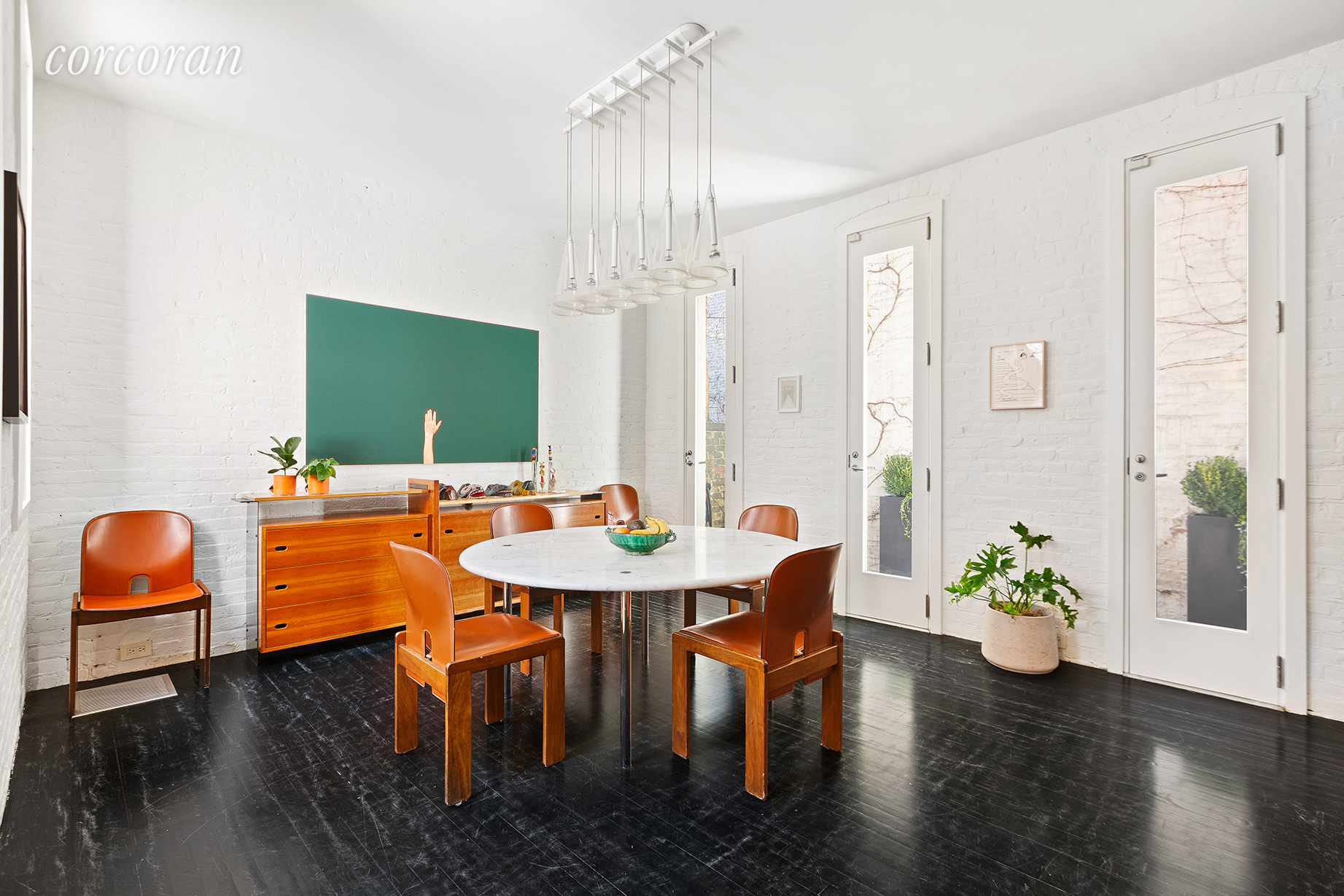 Stained wooden floors and whitewashed brick walls create a clean palette for the property's new owner