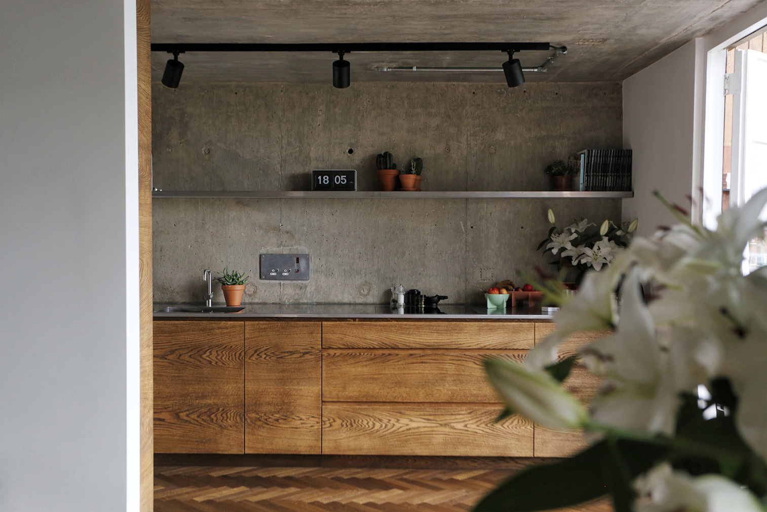 The kitchen and living room have glazed end walls with views over plane trees and direct access to its full-length balcony.