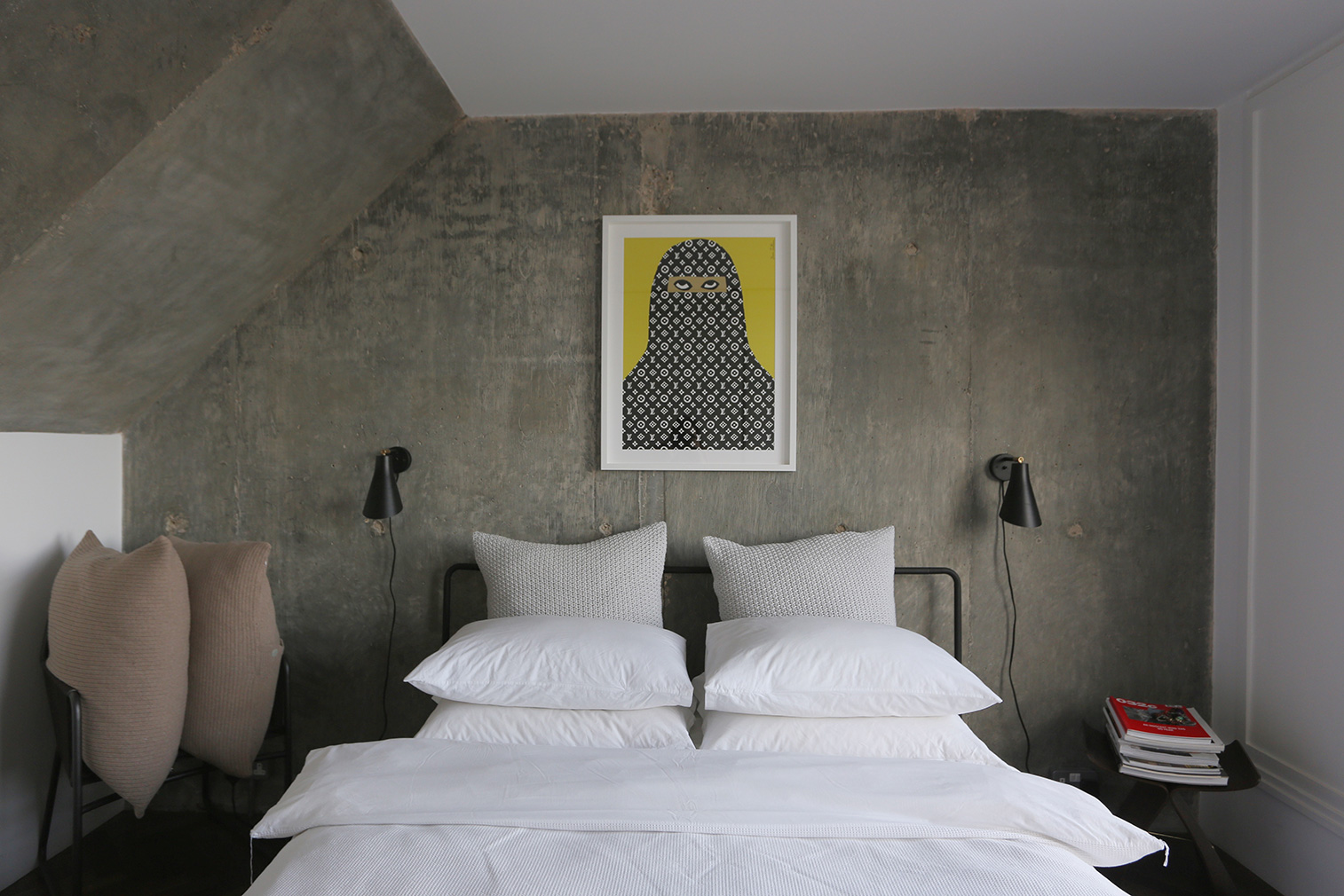 The master bedroom has exposed concrete walls and large picture windows