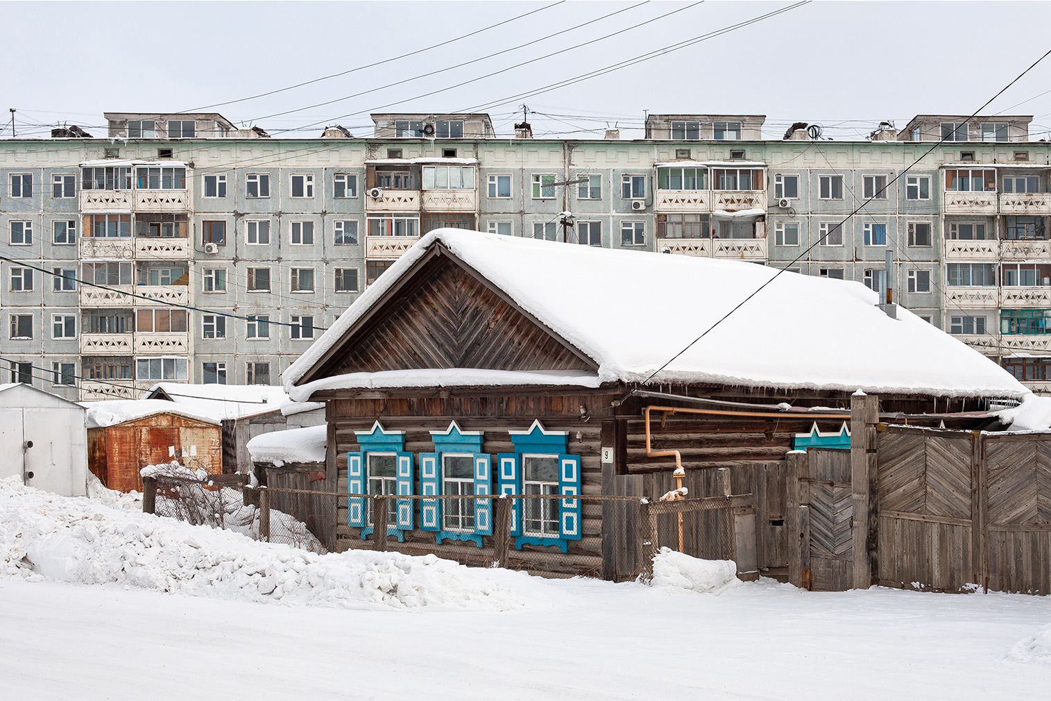 A typical Yakutian Izba and a prefab panel block from the late 1980s. Photography: Alexander Veryovkin © Zupagrafika, 2020