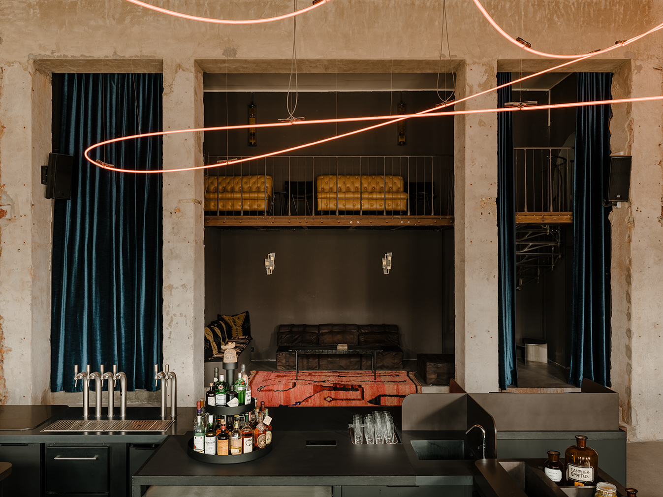 Kink bar in Berlin. The former brewery complex is now home to a moody and industrial inspired bar named Kink. Plaster and brick are contrasted by heavy velvet drapes, colourful floor cushions and a collection of art including a 100-ft-long neon rope installation by Kerim Seiler