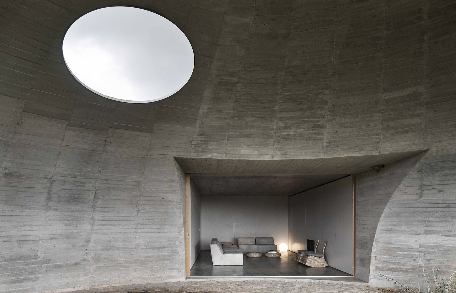 Casa na Terra or 'House in the Earth' is a concrete volume with geometric voids carved out of it to create monastic communal spaces and three ensuite bedrooms.