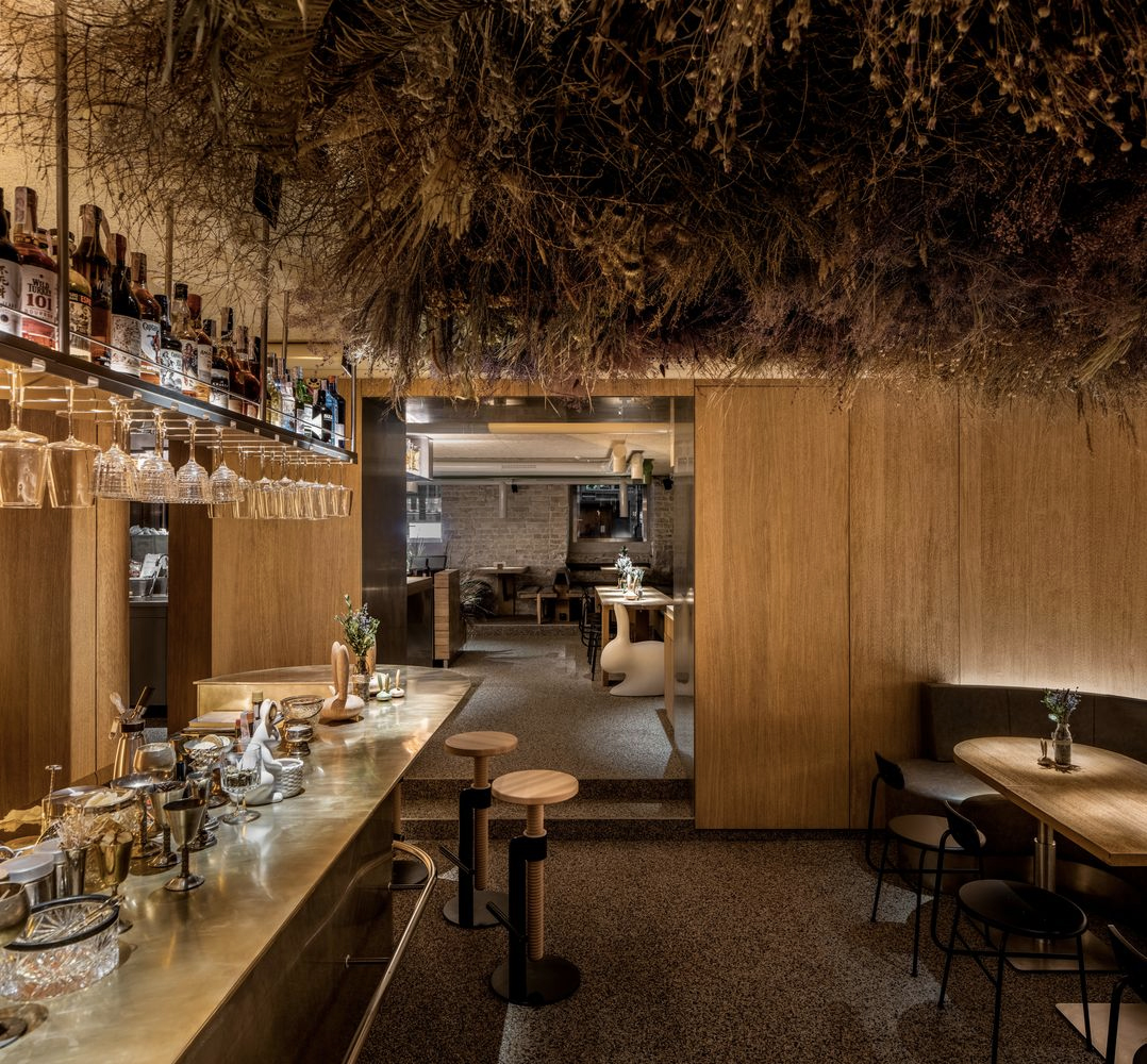 The second of the bar's two main spaces features a striking art installation, made up of dried herbs, flowers and grasses that appear to be growing out of the ceiling overhead to haunting effect