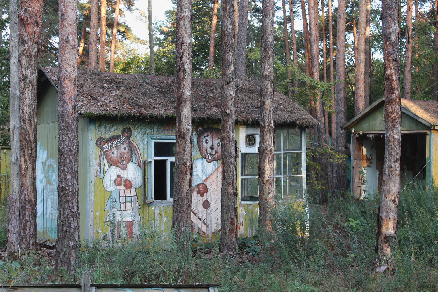 Izumrudniy' ('Emerald') Holiday Camp, near Chornobyl. Once a popular spot for summer holiday breaks, these rustic wooden chalets, painted with characters from cartoons and fairy tales, were completely destroyed by forest fires in April 2020. © Darmon Richter / FUEL Publishing