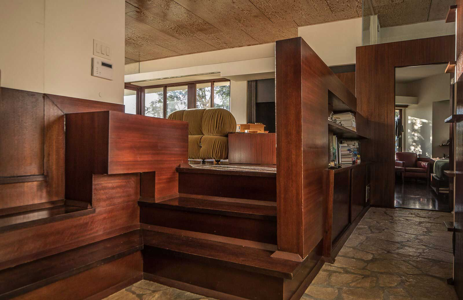 The penthouse apartment has original mahogany cabinetry and stairs, as well as period plywood ceilings