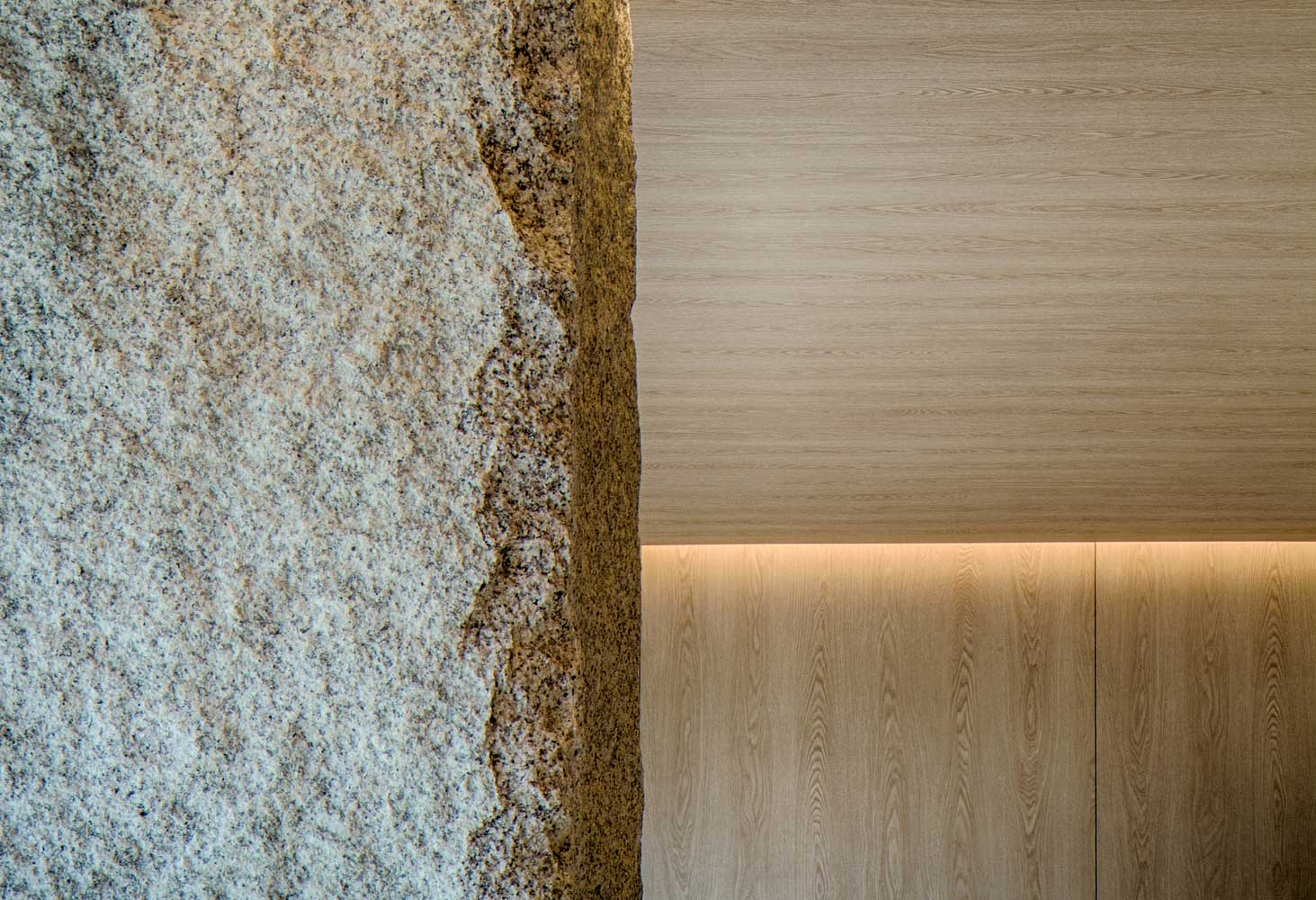 A stone pillar juts into the yoga studio offering structural support for the building and connecting the manmade with the natural