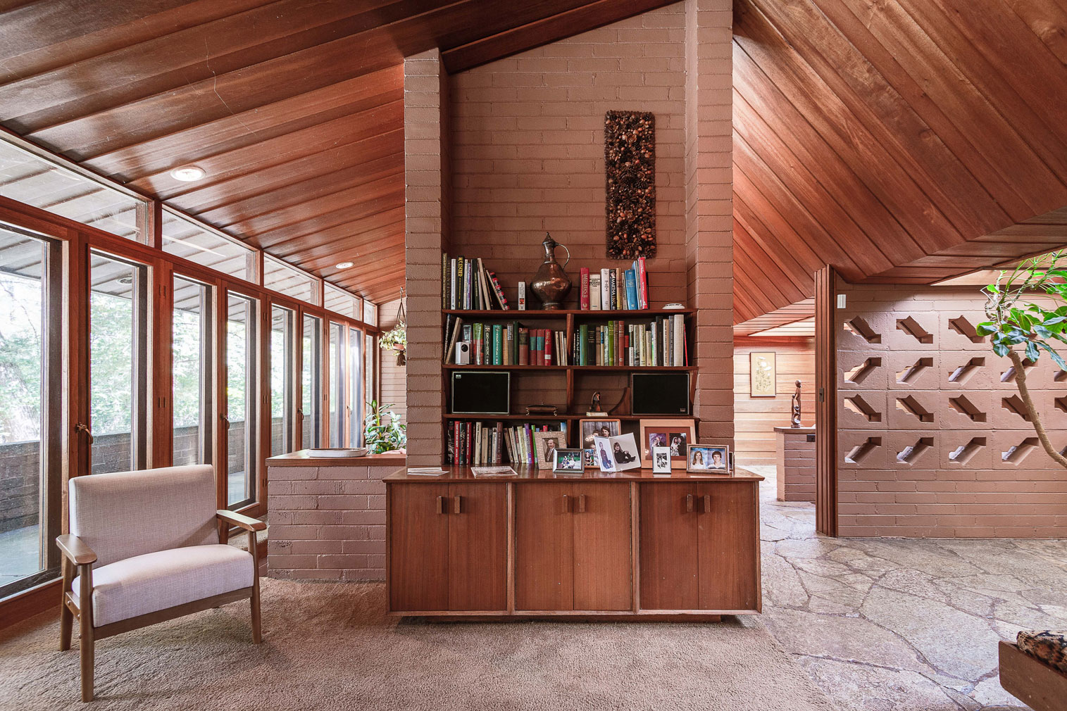 Brick walls have geometric cut outs and support sloping mahogany ceilings