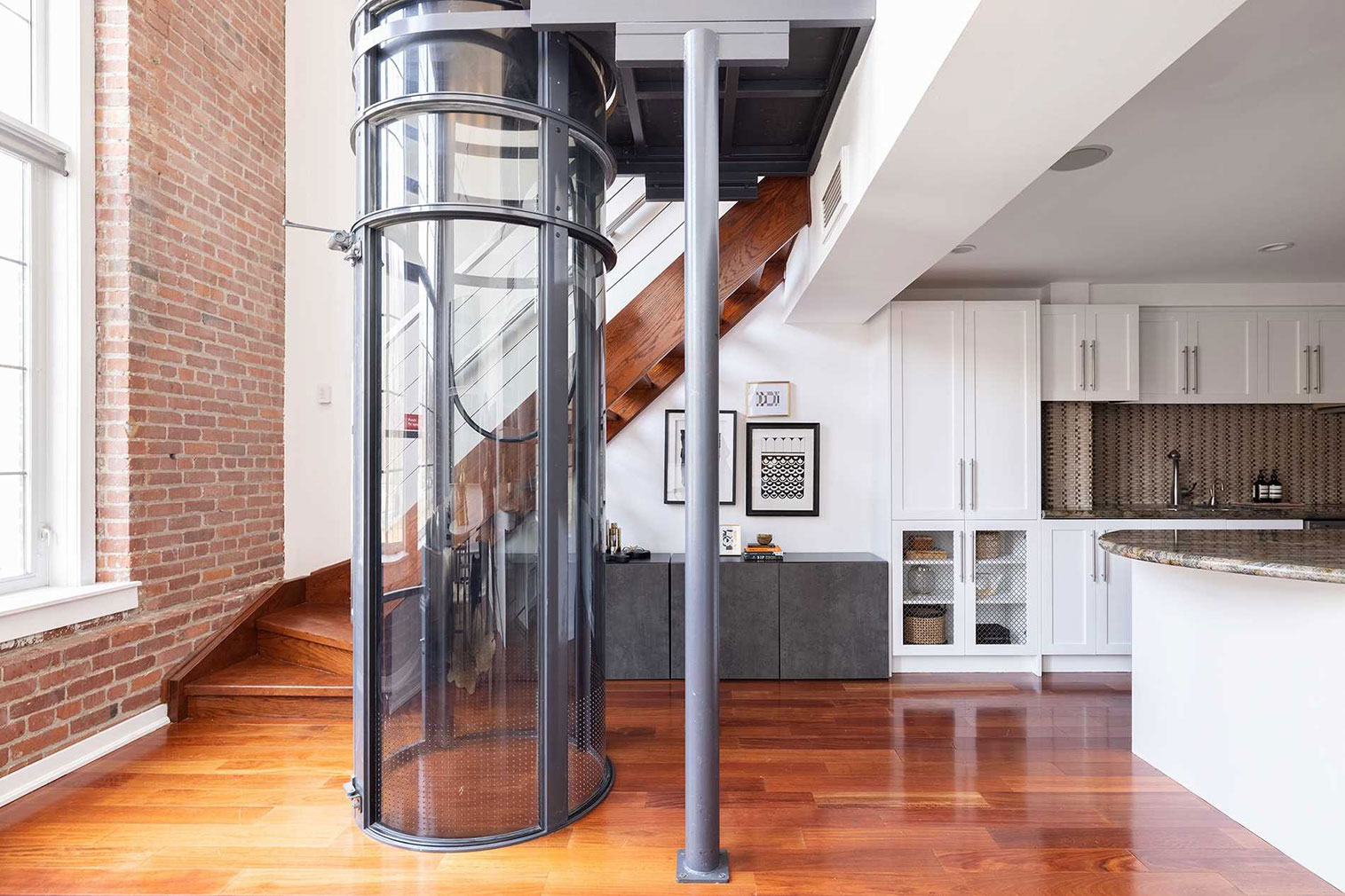 The apartment is serviced by a glass-enclosed elevator