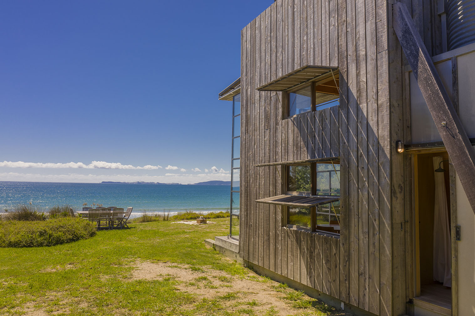 This award-winning New Zealand coastal cabin has been built on wooden runners, limiting impact on its natural environment while enabling it to be easily towed away