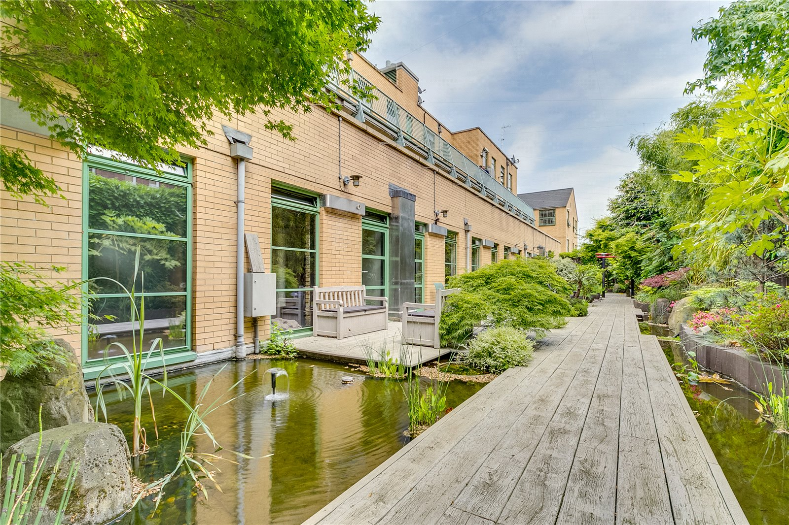 The flat is one of six homes accessed through Japanese water gardens, each with a private bridge to the front door.