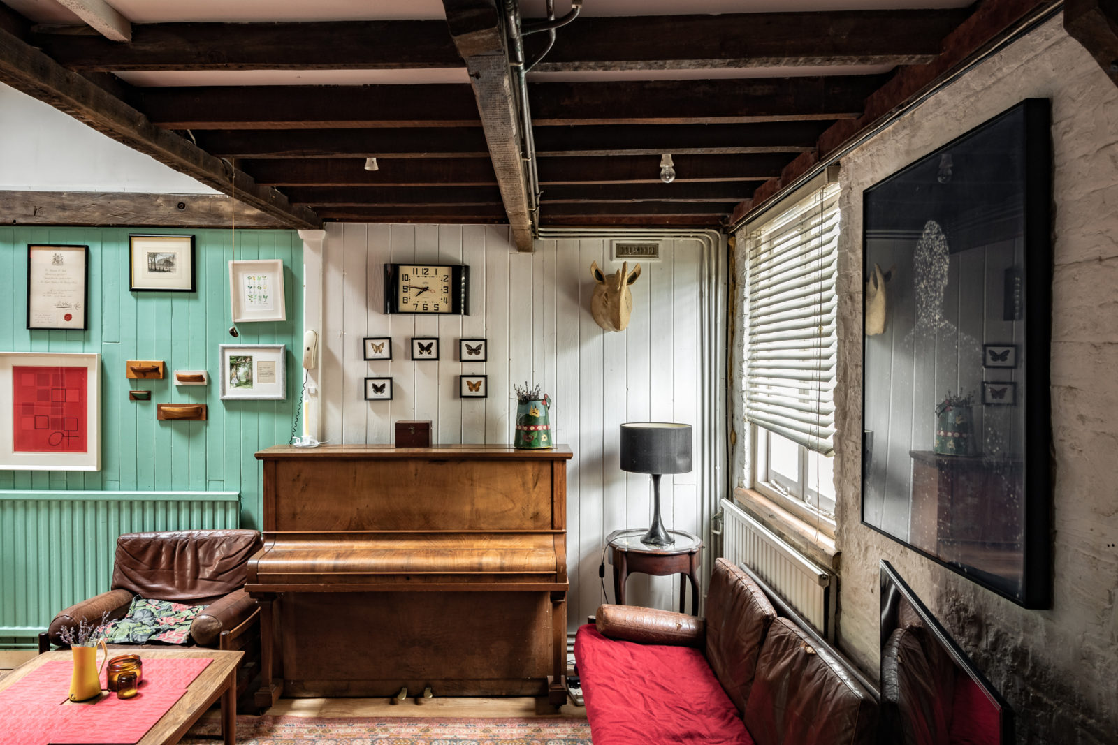 A snug living room is set beneath one of the old raftered haylofts