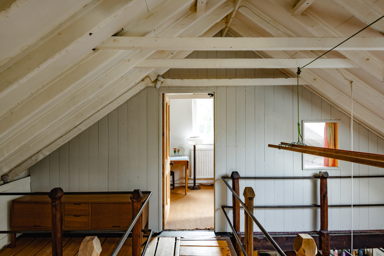 A view through the upper level of the London property, where bedrooms are set beneath the a-frame trusses and eaves of the pitched roof