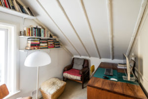 There's a small study set beneath the eaves for a convenient work-from-home set-up