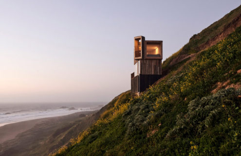 Twin cabins occupy a windy hillside on Chile's coast
