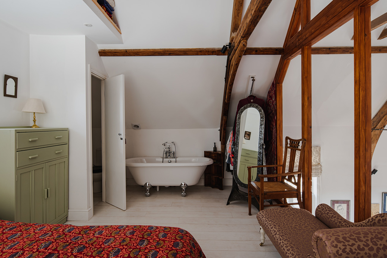 The bedroom has a freestanding bathtub and views straight across the entirely of the converted chapel