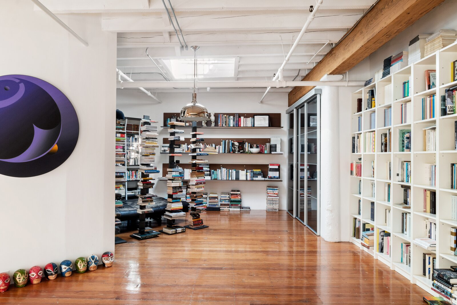 The library features floor-to-ceiling built in shelving and has a skylight roof