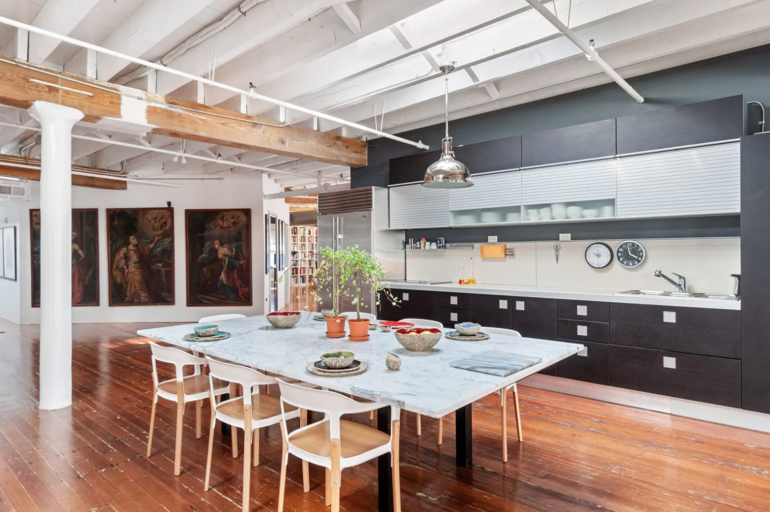 Iron and concrete colums, oak beams and raftered ceilings feature throughout. Meanwhile the kitchen is used as an informal divider to zone off an area of the open floorplan