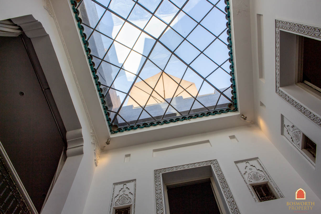The large sun awning can be glimpsed from beneath the grass skylight that covers the courtyard