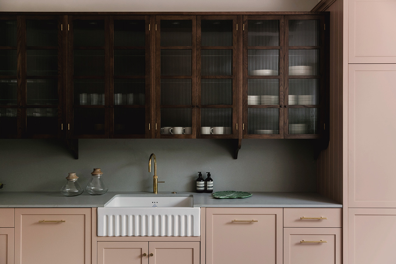 The soothing and serene interiors of Flower Lane's kitchen. Notice how the dark wooden cupboards juxtapose the contemporary dusty pink cabinets and cool green backsplash