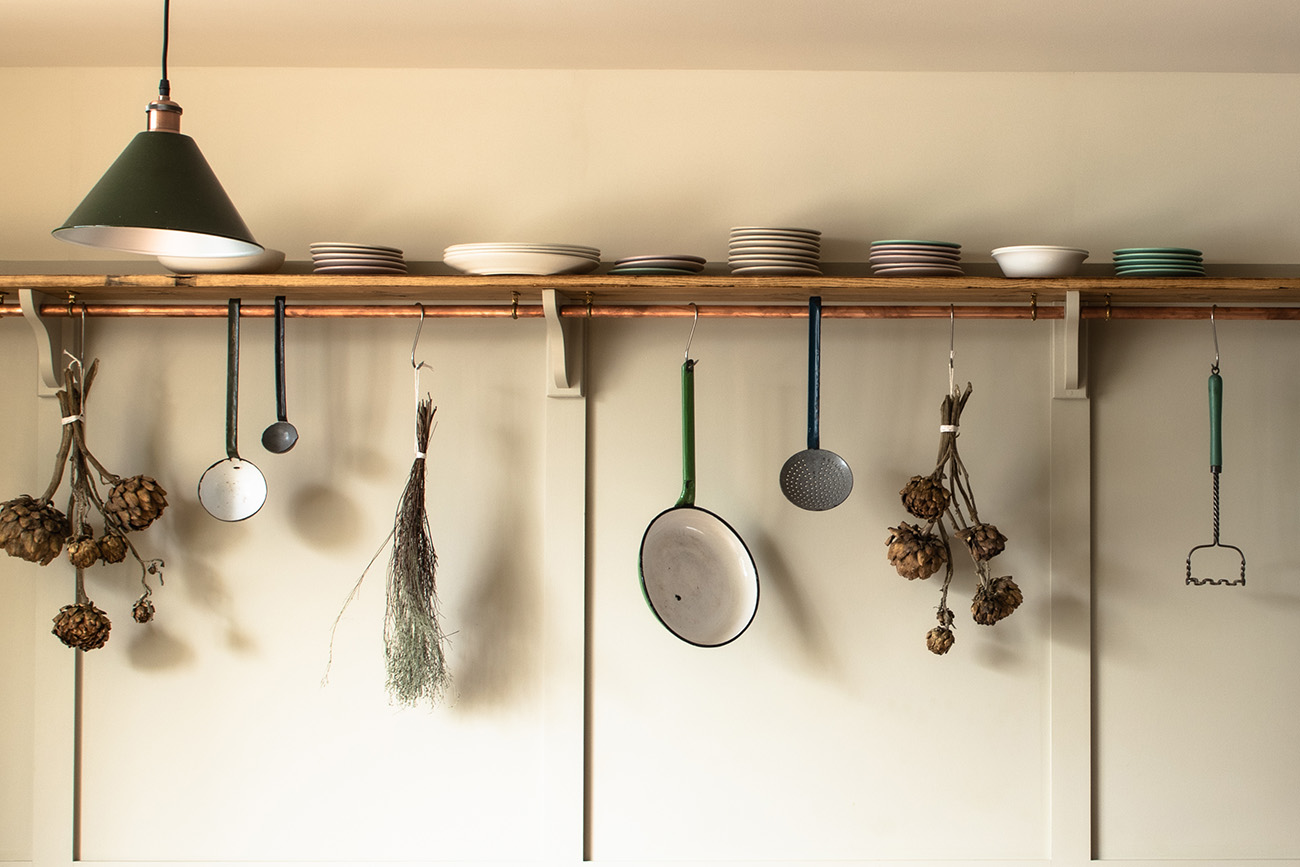 Shelving is mounted high on the wall for hanging ladles, pans and stacking crockery