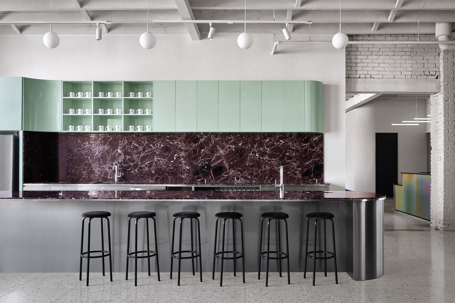 Burgundy features again in the kitchen, this time in the veined backsplash, contrasted by mint green cupboards