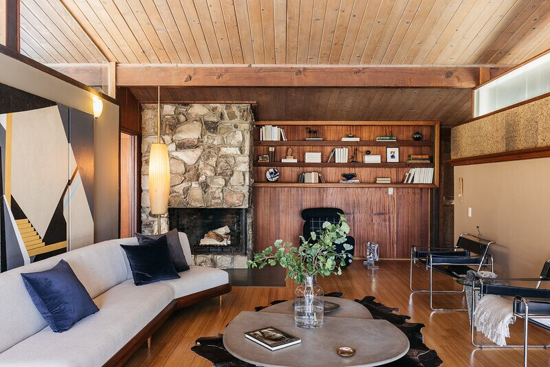 Midcentury details include timber beams and ceilings, clerestory windows, and fieldstone foreplaces