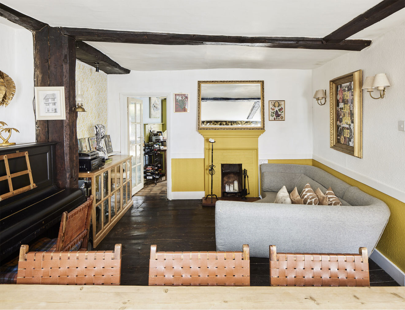 The main living room features an open fireplace and exposed timbers and wood floors
