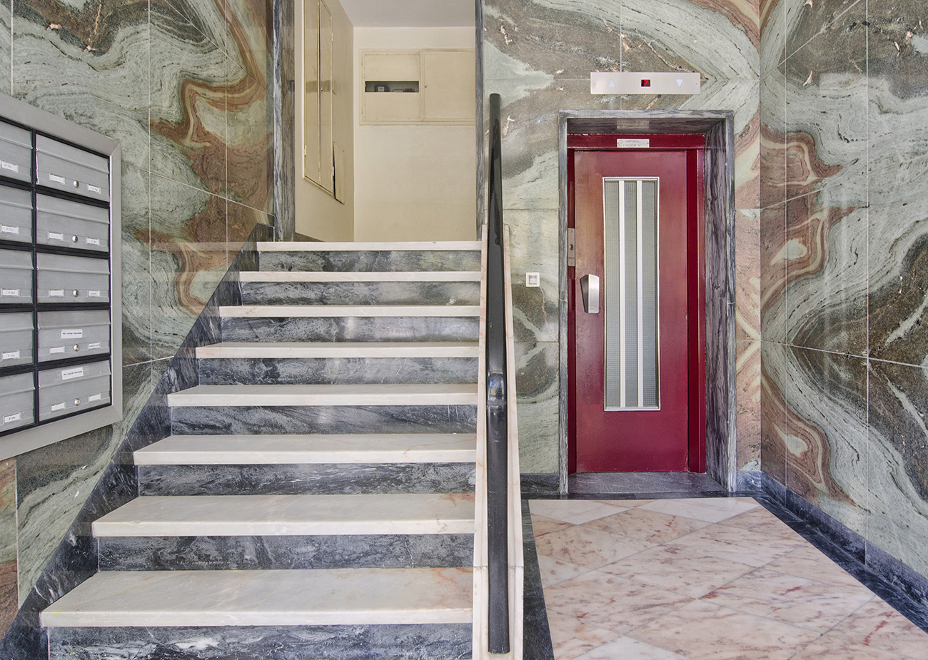 Swirling marble tiles clad the walls of this multi-unit apartment lobby in Lisbon