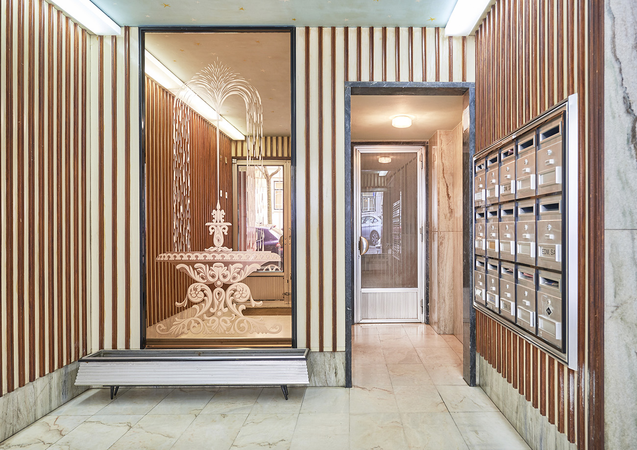 Fluted timber and mirrors hone a glamorous vibe inside this Lisbon apartment building which dates from the 1960s