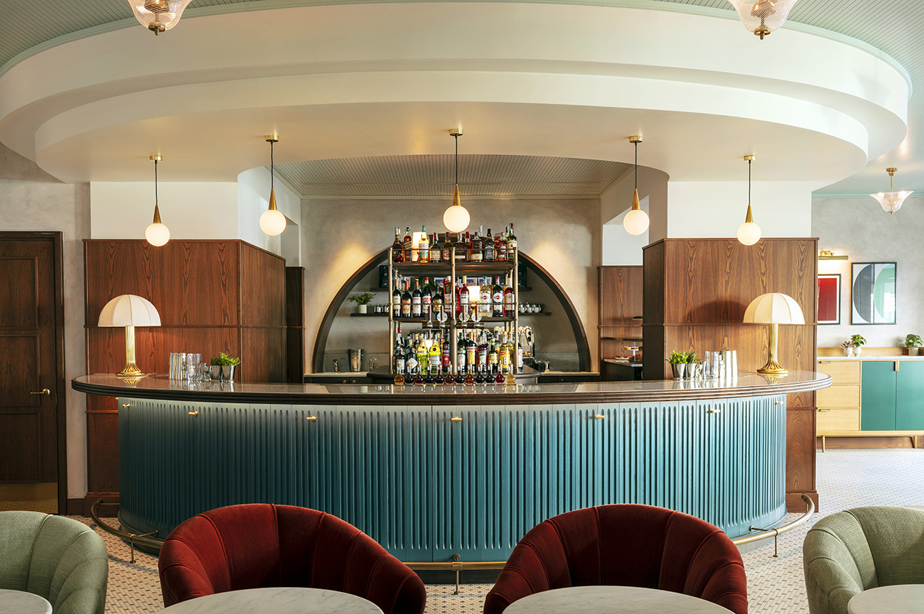 The curved reception desk and bar feature wrapped timber and fluted details.