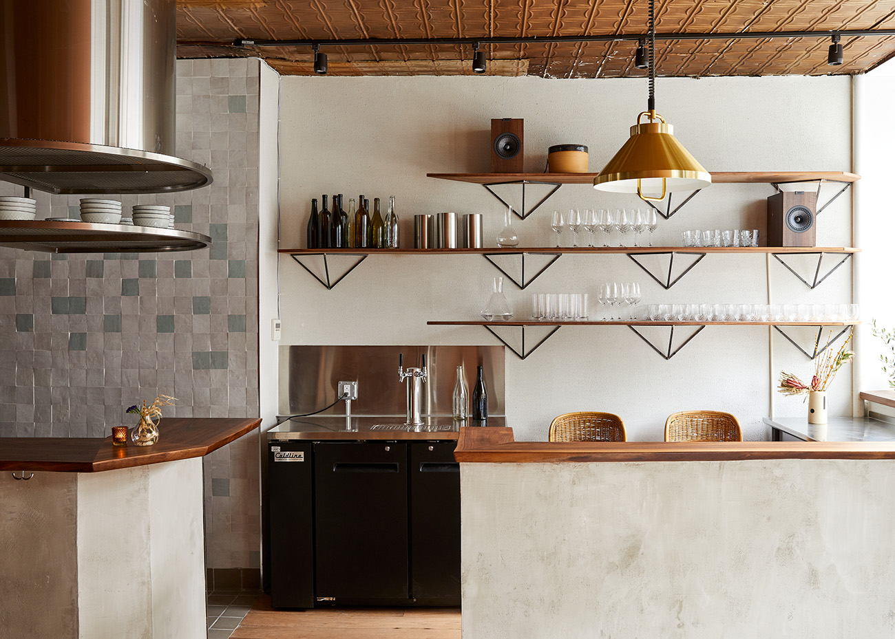Simple interiors are grounded in location via tin plate ceilings and tiles by local studios