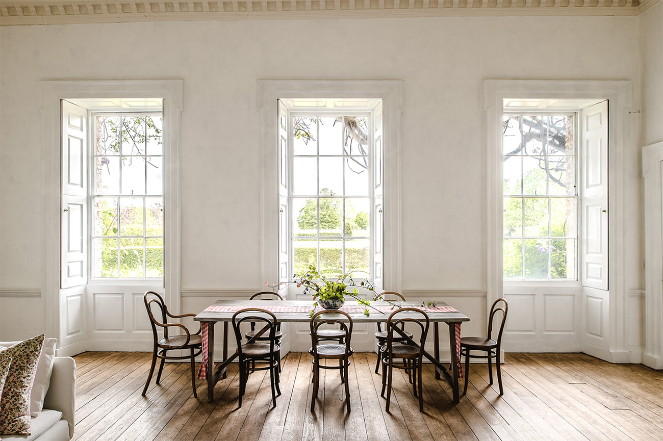 The dining room features triple aspect bay windows, rococo ceilings and stripped floorboards