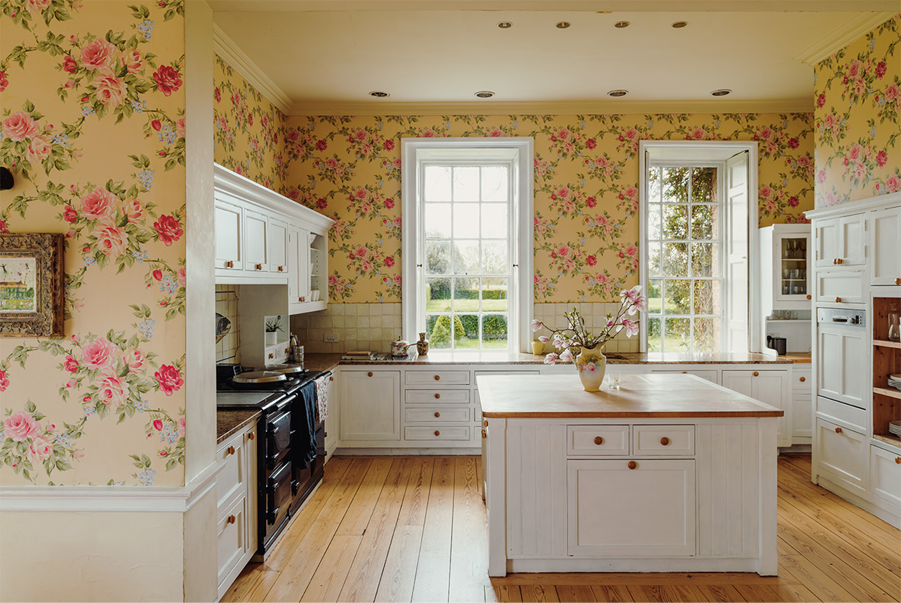 The main family kitchen with Shaker style cabinetry and chintz wallpaper