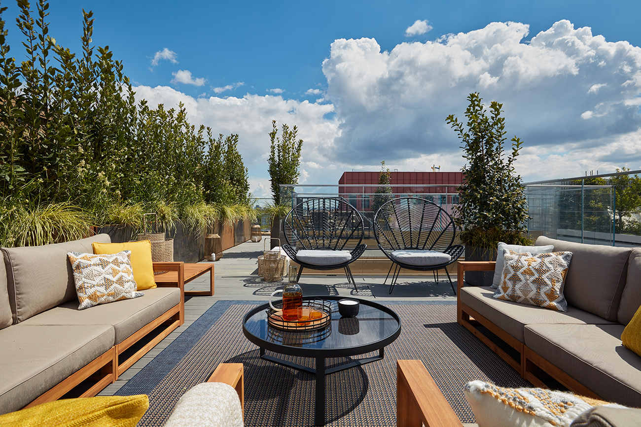 The apartment has a private terrace area with landscaping