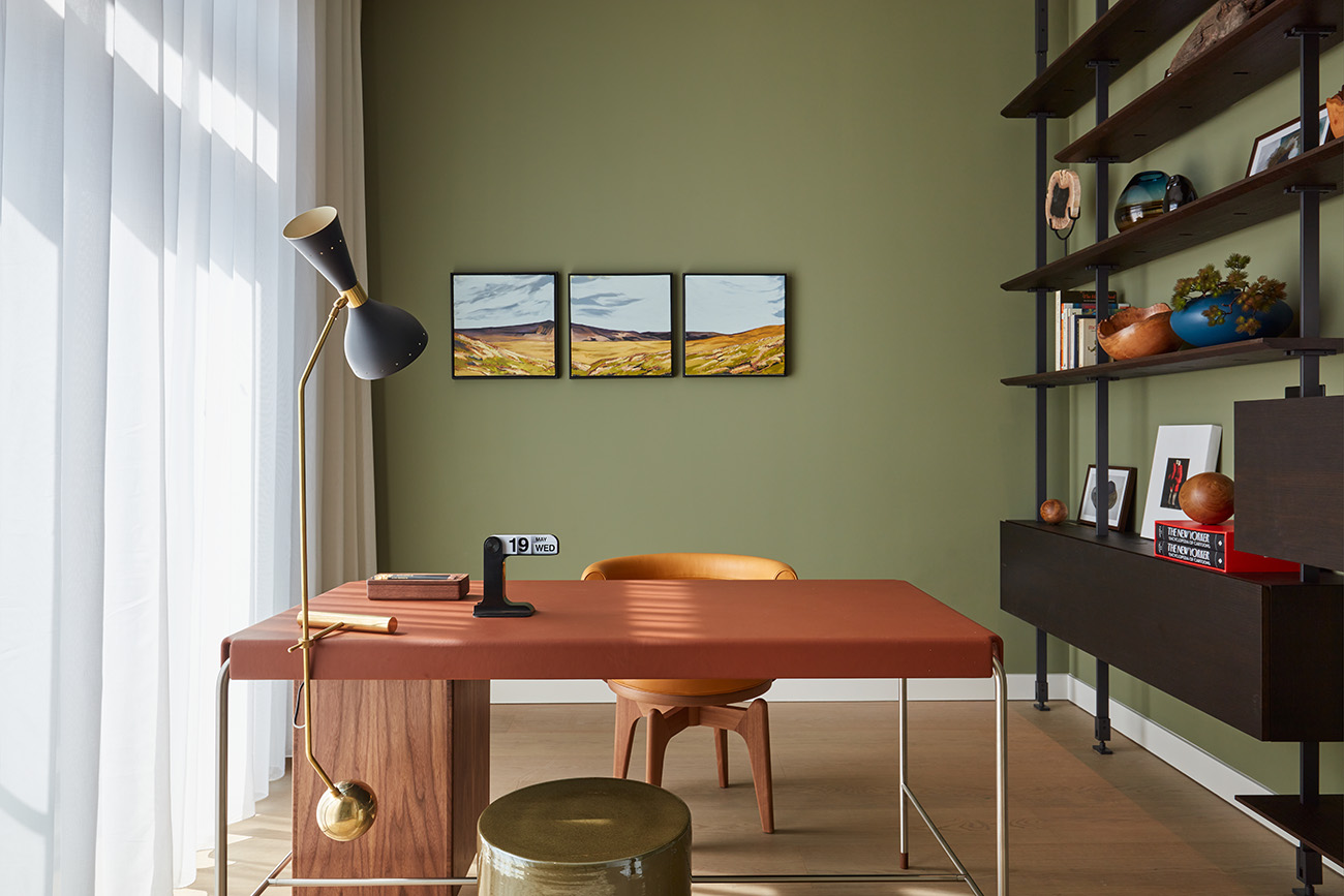 The study area has a midcentury modern vibe thanks to mossy walls and timber shelving