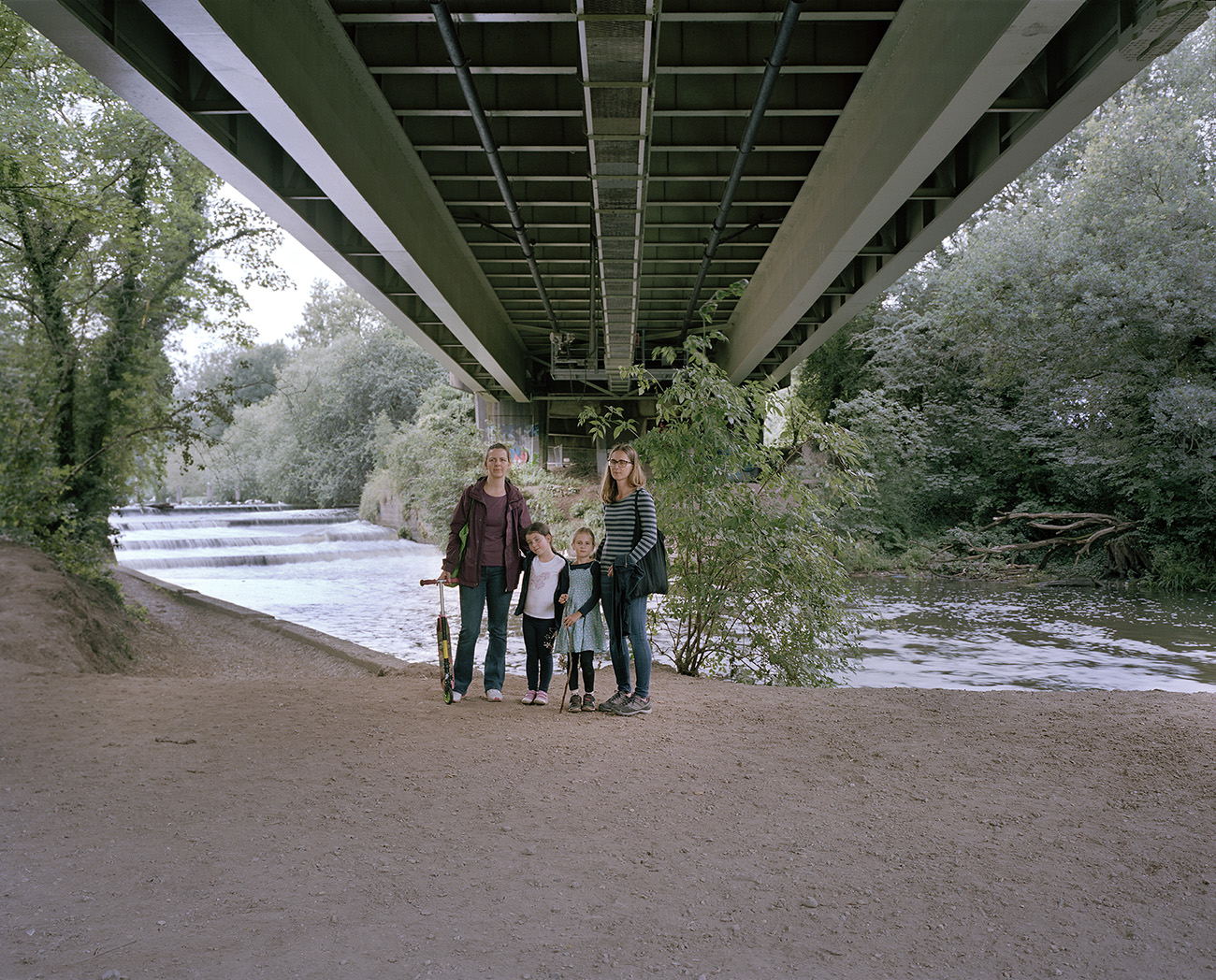 A family photographed by Andrew Meredith beneath the M4 motorway
