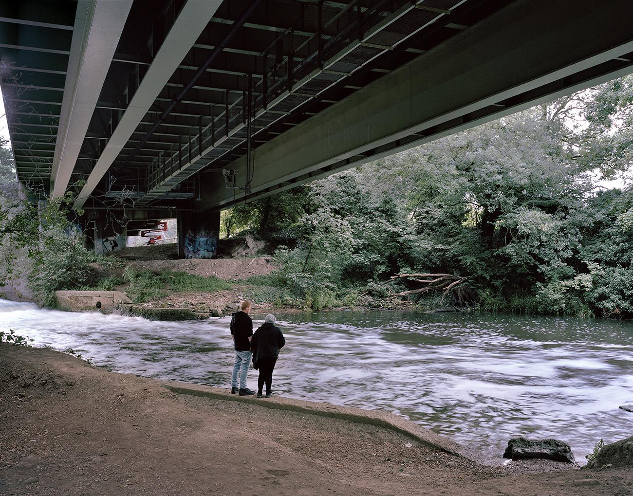 Water coursing beneath the concrete bridge above