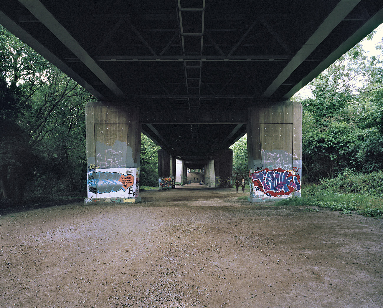 Graffiti and tags cover the concrete pillars of the motorway above