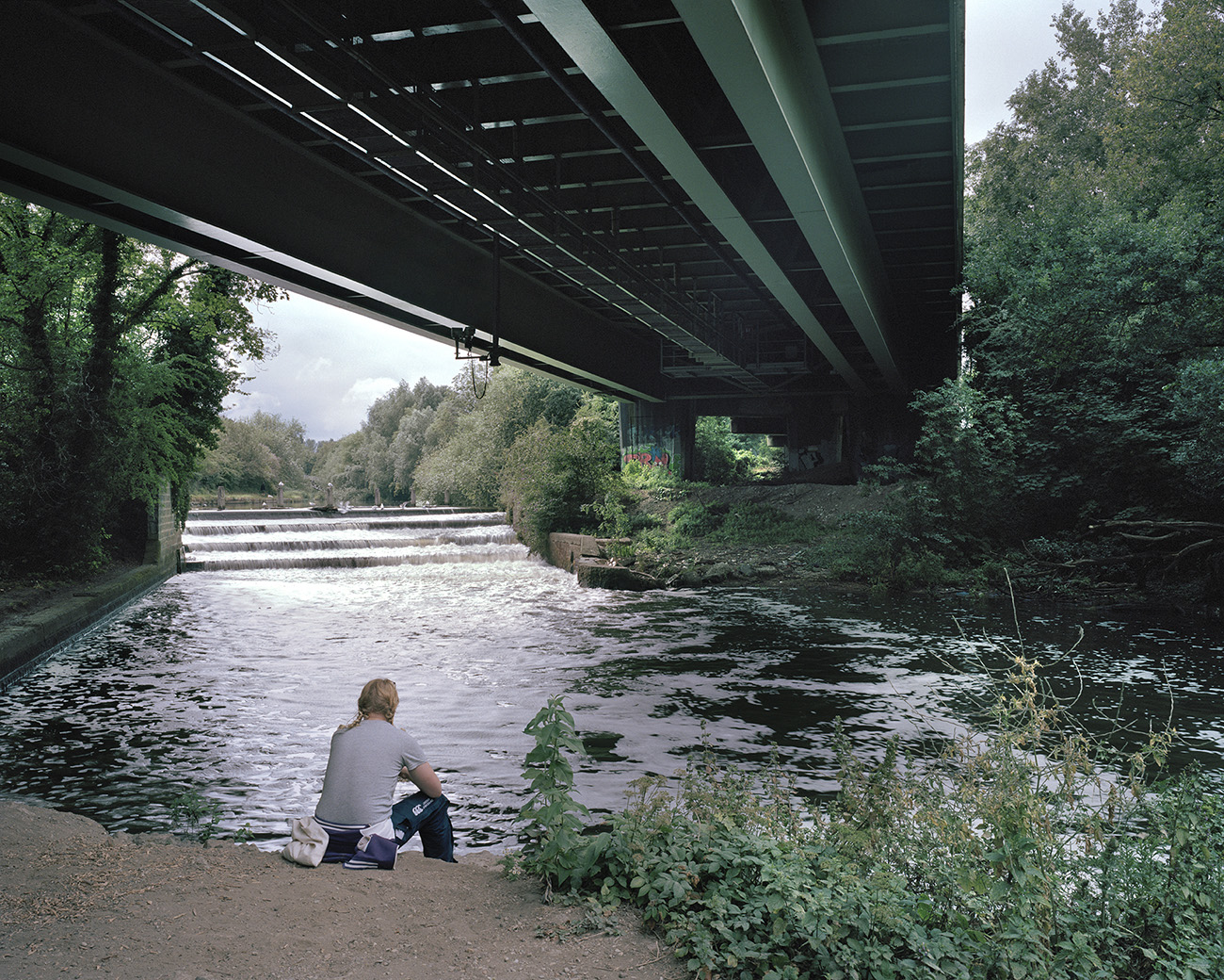 A lone man sits contemplating on the banks of the river, beneath the motorway pass