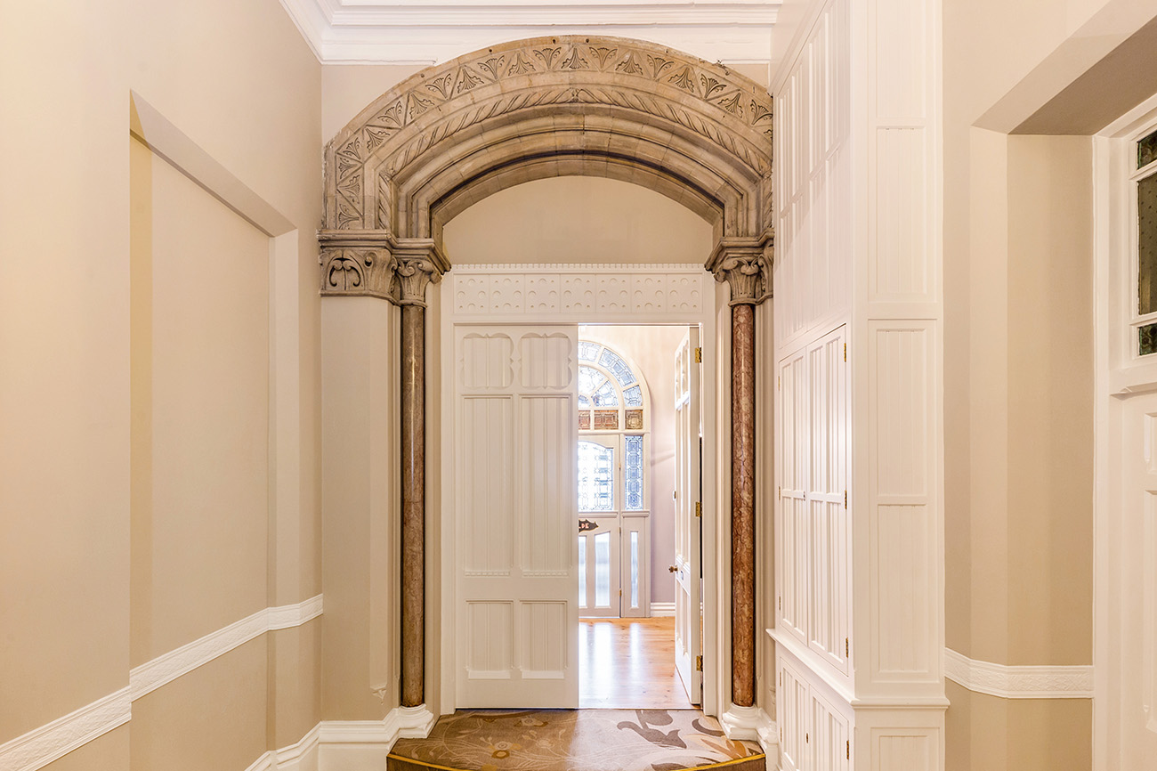 Pilaster-flanked stone arch and carved timber double doors lead into the main space.