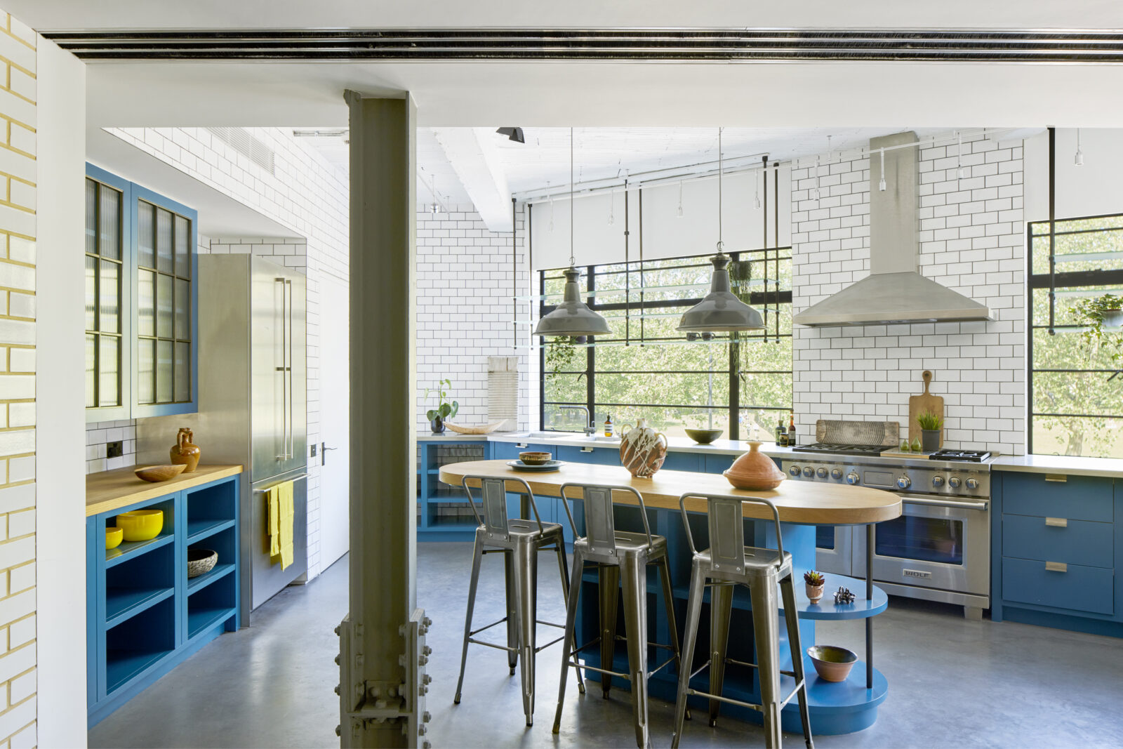 Steel beams, glazed brickwork and bright blue cabinetry in the kitchen