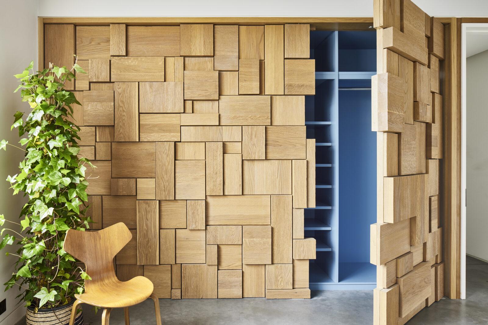 Jigsaw like oak panels reveal concealed wardrobes