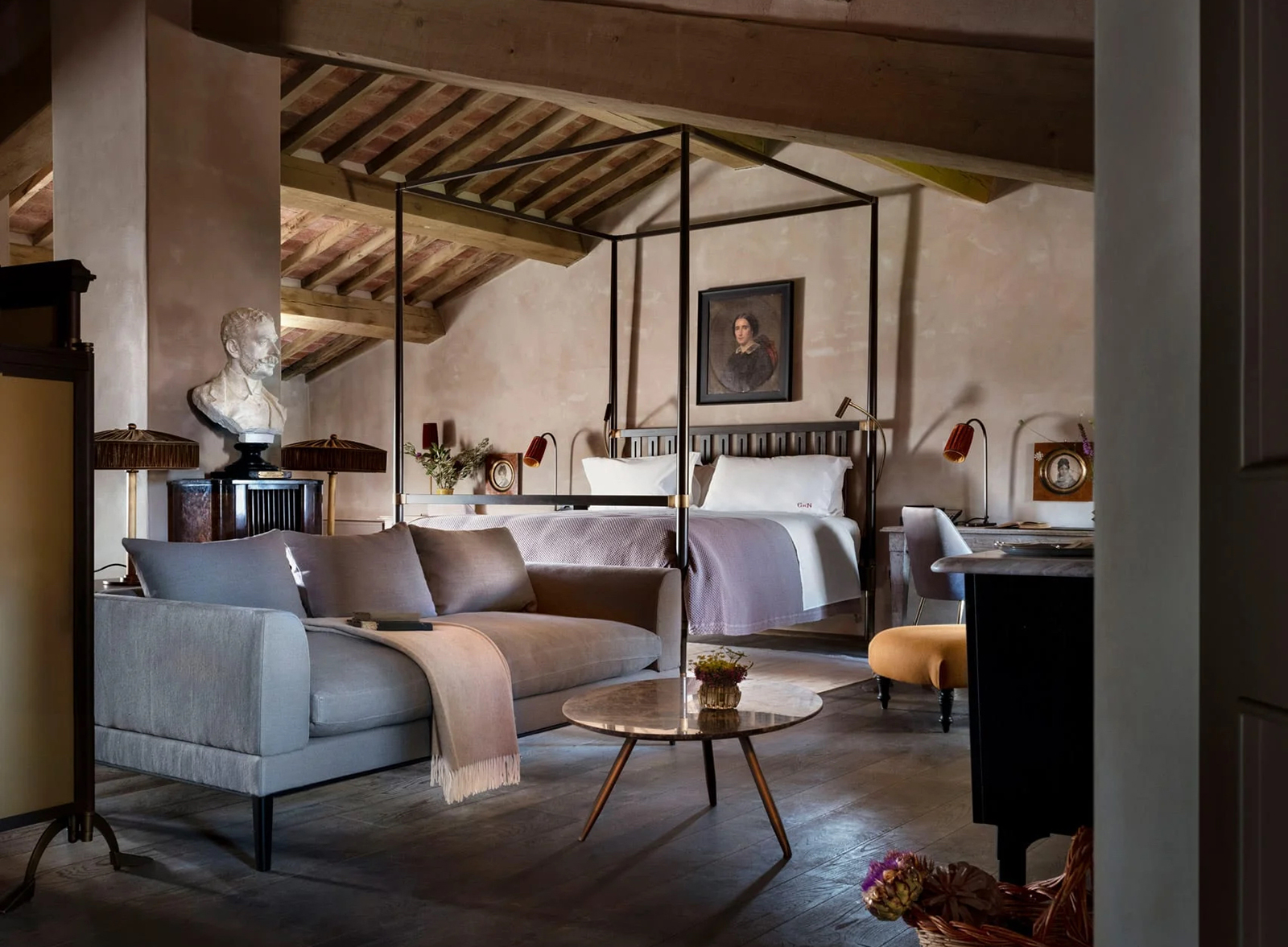 Modern furniture and fabrics sit beneath historic rafters