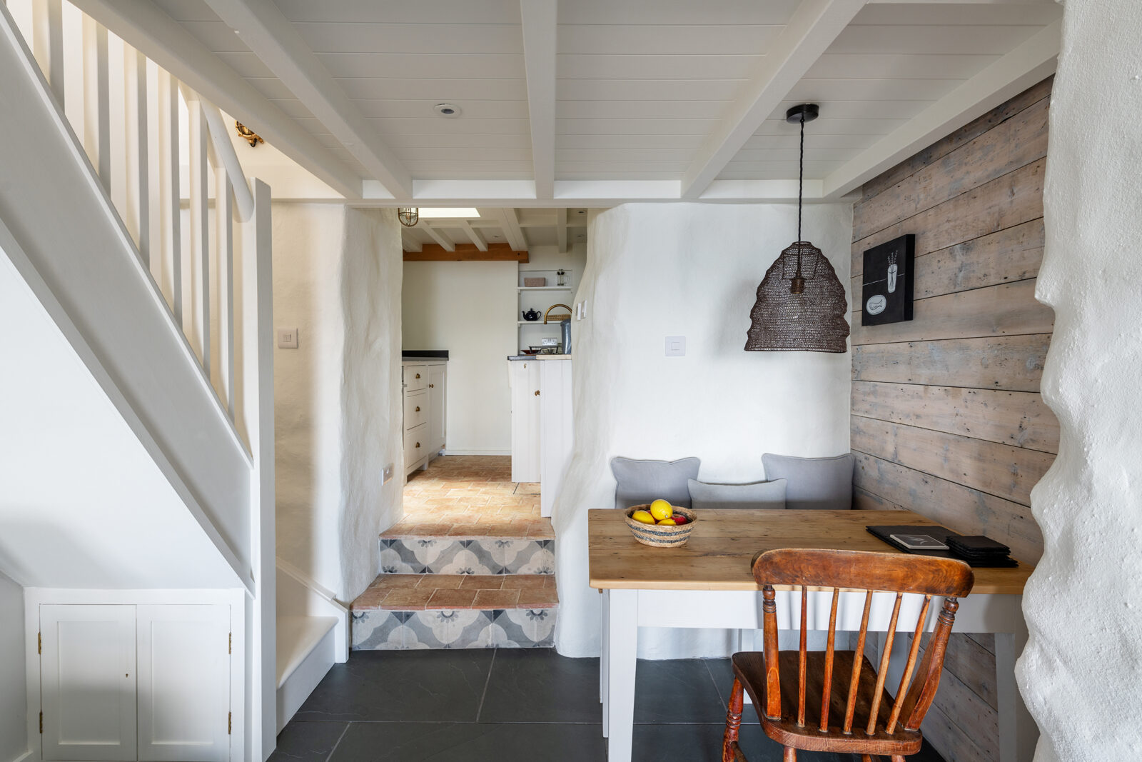The ground floor is largely open plan, comprising the living room, dining nook and galley kitchen
